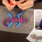 Collage of two photos: one of a purple and blue gecko being made with two hands in the frame, and a photo of Rose standing holding a blue and green gecko.