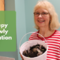 Photo of Mrs. Charles holding a white bucket that contains dirt, worms, and food scraps. She is standing against a teal colored wall.