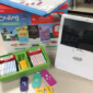 Photo of an Osmo Coding Kit on a tabletop, which consists of a white tablet and stand, game pieces in various colors, an instruction manual and the box it came in.